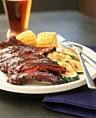Barbecue Ribs on a Plate with Zucchini and Corn on the Cob; Beer