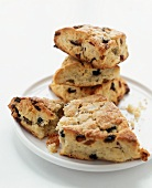 Scones with Dried Fruit on a Plate; Three Stacked; One Broken