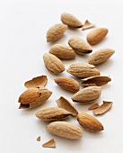 Many Whole and Shelled Almonds on a White Background