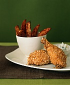 Crispy Chicken Drumsticks on a Plate with a Bowl of Oven Fries