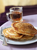 Three pancakes and a small jug of maple syrup
