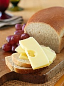 A few slices of semi-hard cheese, white bread and grapes
