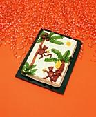 Monkey Cake with Orange Party Ribbons on an Orange Background