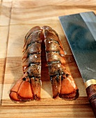 Lobster Tail Halved on a Cutting Board; Knife