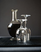 Two Empty Wine Glasses Turned Upside Down; Carafe of Red Wine