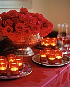 Table with Many lit Candles and Red Rose Centerpiece
