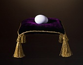 A White Egg on a Velvet Pillow with Tassels