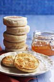 A Stack of English Muffins, One Toasted, and a Jar of Marmalade