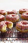 Pink Frosted Doughnuts with Sprinkles on a Cooling Rack; One Bitten