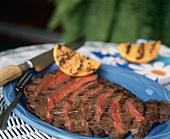 Sliced Grilled Flank Steak on a Blue Platter
