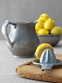Zitronenpresse mit einer Kanne und einer Schüssel Zitronen
