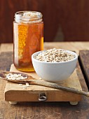 Bowl of Oats with Jar of Honey