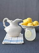 Glass of Lemonade with Pitcher and Fresh Lemons
