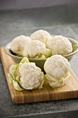 Heads of Baby Cauliflower in a Metal Bowl on Cutting Board
