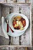 Streifenbarsch mit Muscheln, Oliven und Chorizo