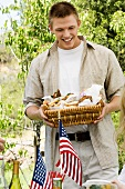 Man Holding a Basket of Sandwiches at 4th of July Picnic