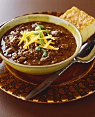 Bowl of Chili with Shredded Cheese and Corn Bread