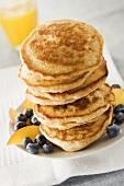 Tall Stack of Pancakes with Fresh Blueberries and Peachs