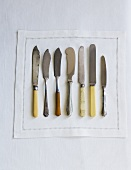 Variety of Knives on a White Napkin