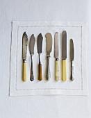 Verschiedene Messer auf Stoffserviette (Draufsicht)