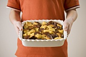 Child Holding Baking Dish of Bread Pudding