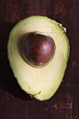 Half an Avocado with Pit on Wood