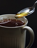 Spooning Honey into a Cup of Tea
