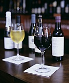 Glasses of Red and White Wine with Bottles on Bar