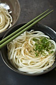 Bowl of Udon Soup with Green Onion and Sesame Seeds; Chopsticks