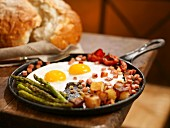 Breakfast Skillet with Fried Eggs, Diced Ham, Potatoes and Asparagus