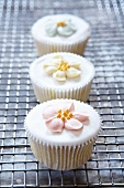 Three Cupcakes with Frosting Flowers on a Cooling Rack