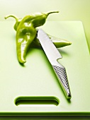 Two Green Chili Peppers on Cutting Board with Knife
