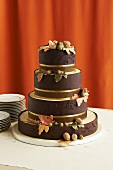 Brown Chocolate Wedding Cake Decorated with Fall Flowers and Nuts