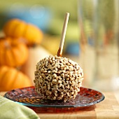 Toffee apple coated with nuts on a plate