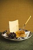 Käsestück, Früchte und Honig auf Teller