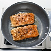 Two Salmon Fillets Cooking in Skillet