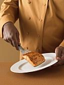 Koch legt gebratenes Lachsfilet auf Teller