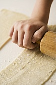 Child Rolling Dough with Wooden Rolling Pin