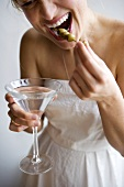 Woman in White Dress Holding Martini and Eating Olives