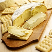 Sliced Brie Cheese with Crackers on Wooden Cheese Board