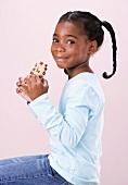 Mädchen hält angebissenen chocolate chip cookie in den Händen