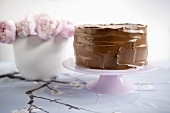 Chocolate Frosted Cake on Pedestal Dish; Pink Flowers