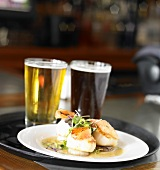 A Restaurant Tray with Seared Scallops and Dark & Light Beers