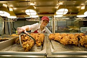 Woman Selecting Piece of Fried Chicken  From Under Heat Lamps