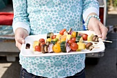 Woman Holding Grilled Fruit and Vegetable Kabobs