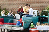 Friends Having a Tailgating Party in the Back of a Pickup Truck
