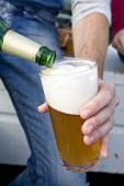 Mann schenkt ein Glas Bier ein