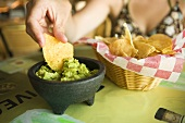 Woman Dipping Corn Chip into Guacamole