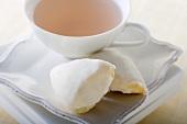 Eine Tasse Rosentee und Scones mit Zitronenglasur