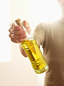 Man Holding a Bottle of Olive Oil; Sunlight